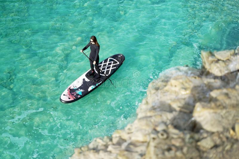 Woman Paddling on SUP board. In a blue sea royalty free stock photo