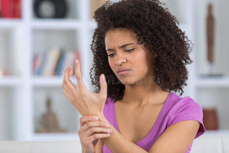 Woman with pain in wrist. Woman with pain in her wrist royalty free stock photo