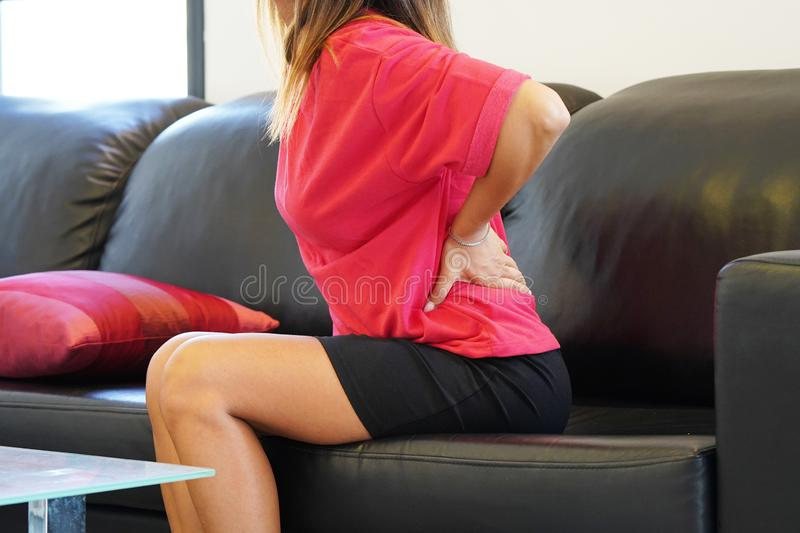 Woman, pain at lower back. Close-up view of a young woman with pain in kidneys at home on couch. Young woman with back ache clasping her hand to her lower back royalty free stock photos