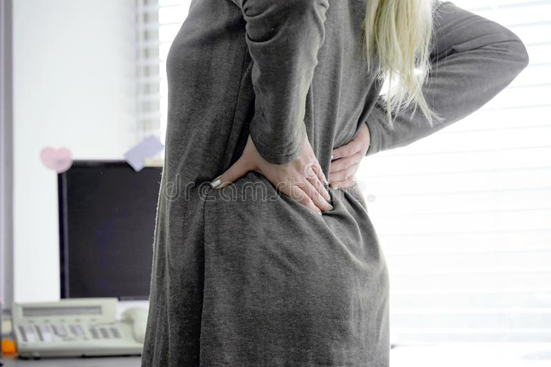 Woman, pain at lower back. Office worker woman with pain in kidneys. Young woman with back ache clasping her hand to her lower back. Woman suffering from ribbing stock photos