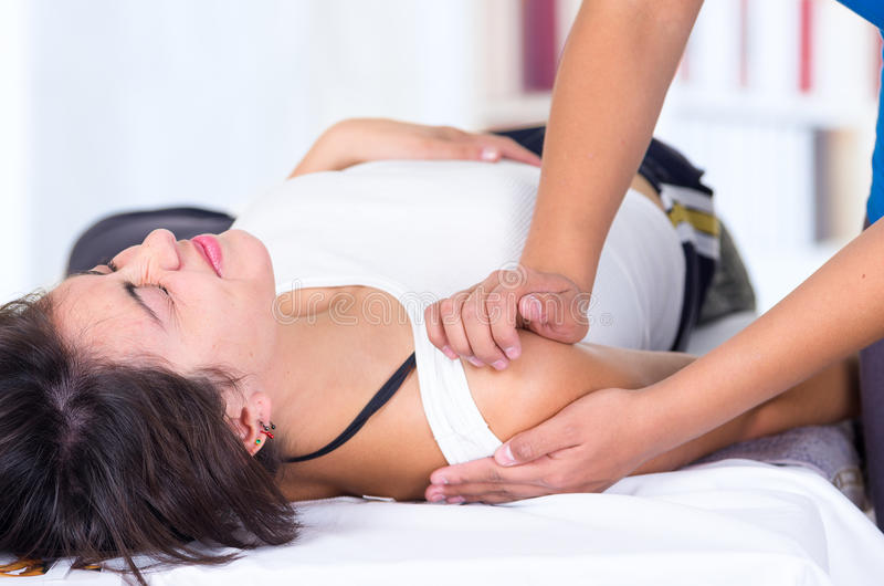 Woman in pain lying while getting a shoulder royalty free stock images