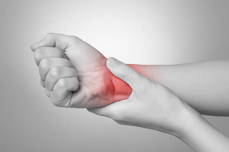 Woman with painful wrist. A young woman holding her painful wrist royalty free stock image