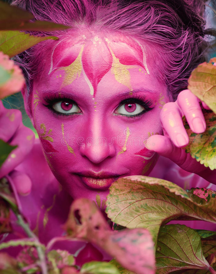 Woman in paint. Attractive and girl body art. Woman in pink paint. Attractive and girl. Face art. Bright make up and body art. Flowers ornament. jungle royalty free stock image