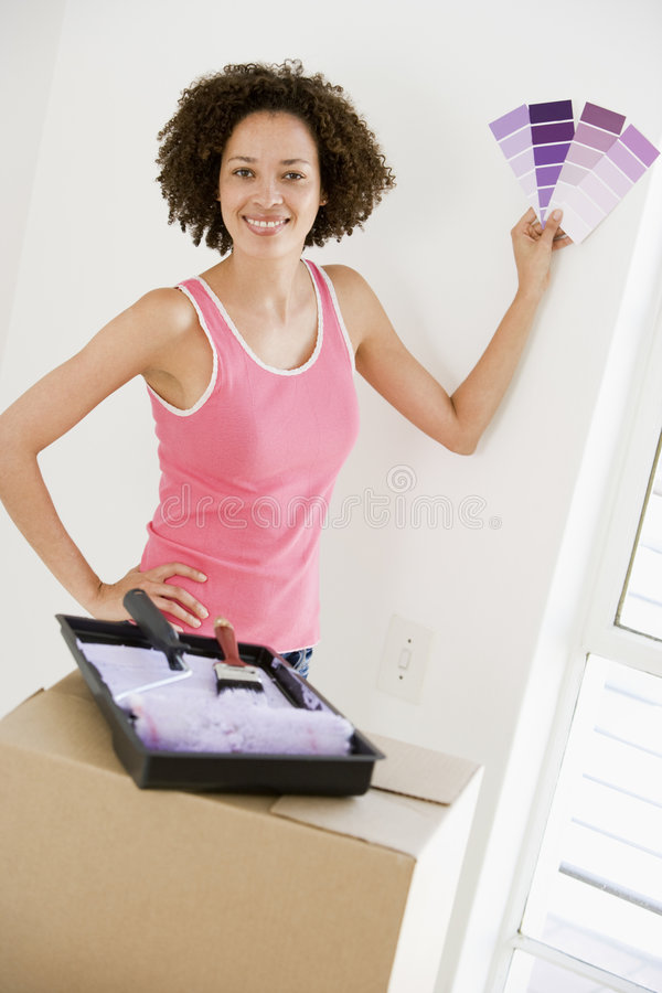 Woman with paint swatches in new home smiling. At camera stock photos
