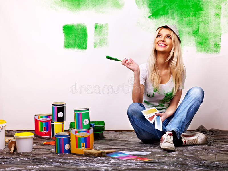 Woman paint wall at home. royalty free stock images