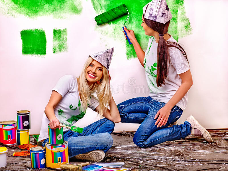 Woman paint wall at home. royalty free stock photography