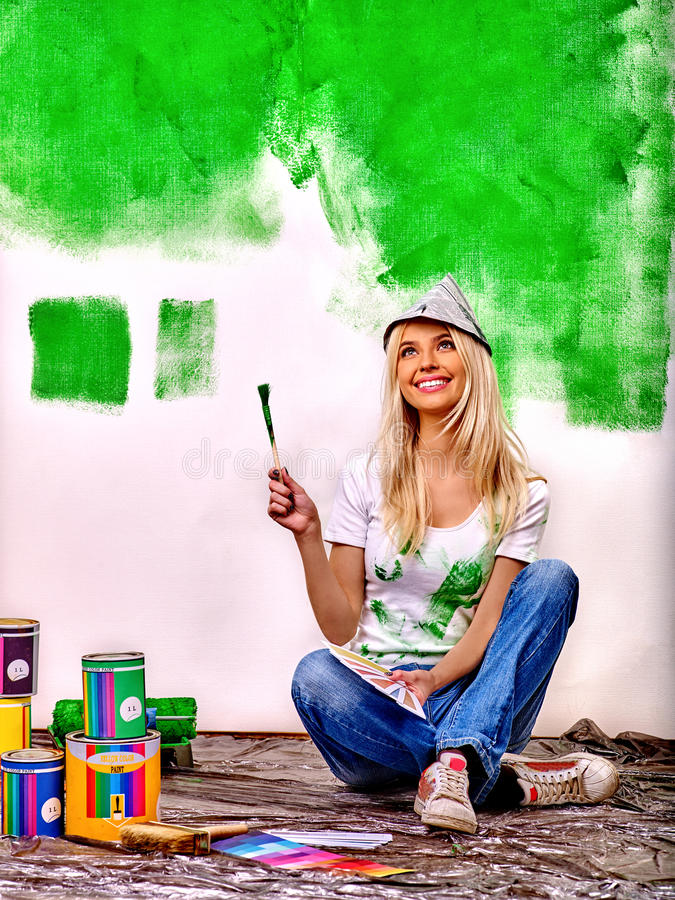 Woman paint wall at home. stock photo