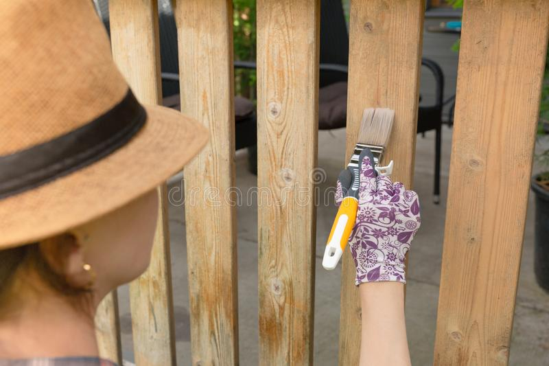 Woman with a paintbrush painting wooden terrace railings. Outdoor shot. In natural light royalty free stock photography