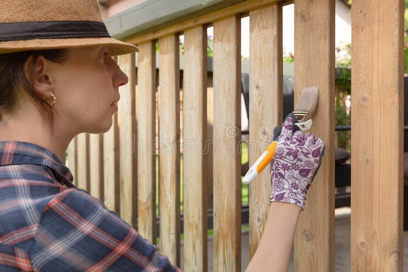 Woman with a paintbrush painting wooden terrace railings. Outdoor shot. In natural light stock photography
