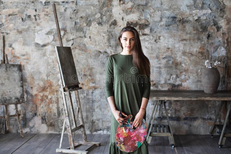 Woman painter in a green dress with a brush and a palette in an art studio. Hobby royalty free stock image