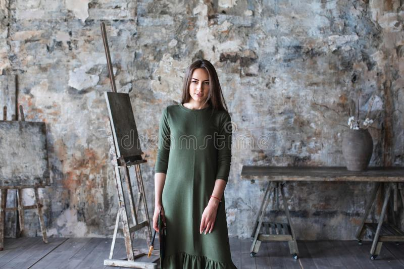 Woman painter in a green dress with a brush and a palette photographed in an art studio royalty free stock photos