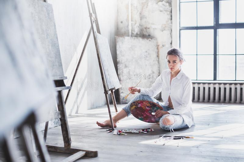 Woman painter painting at workspace. stock images