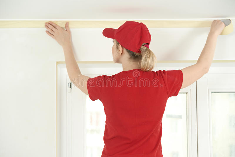 Home Painter with masking tape. Woman painter worker protecting ceiling moulding with masking tape before painting at home improvement work royalty free stock photos