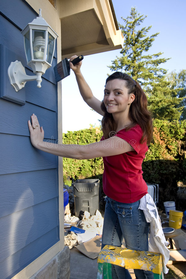 Woman Painting a Blue House - Vertical stock image