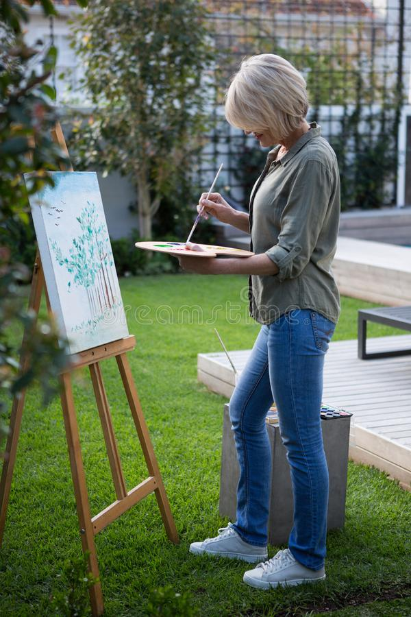 Woman painting on canvas. In lawn stock photos