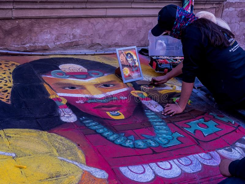 Woman painting with colored chalk an illustration on the floor in the streets of Guanajuato Mexico royalty free stock photography