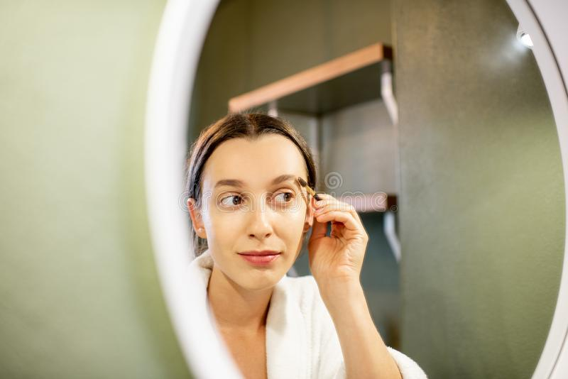 Woman painting eyebrows. Woman in bathrobe painting eyebrows near the round mirror on the green wall of the bathroom royalty free stock images