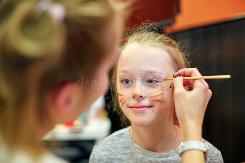 Woman painting face of kid outdoors. baby face painting stock photos