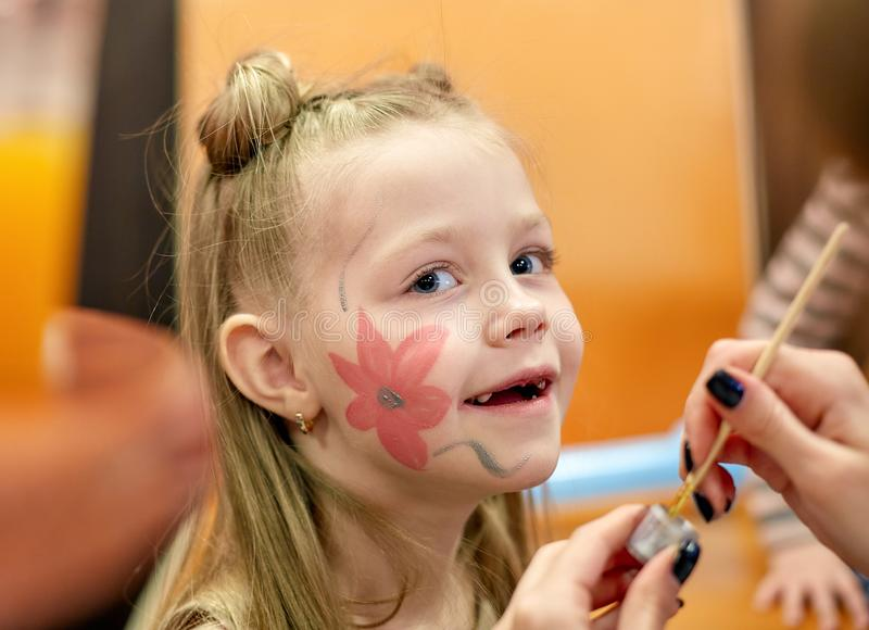 Woman painting face of kid outdoors. baby face painting royalty free stock photography