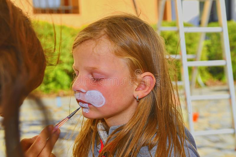 Woman painting face of kid outdoors. Baby face painting. Little girl getting her face painted like a rabbit by face painting artis stock photography