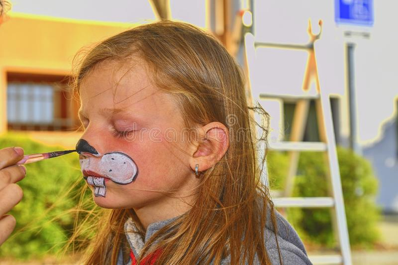 Woman painting face of kid outdoors. Baby face painting. Little girl getting her face painted like a rabbit by face painting artis royalty free stock images