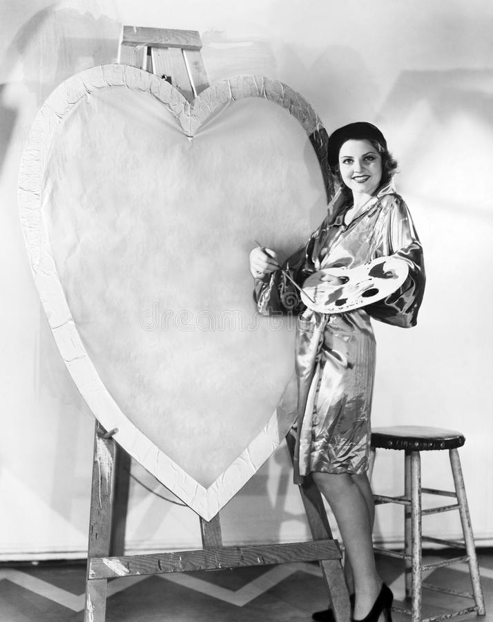 Woman painting huge valentine. (All persons depicted are no longer living and no estate exists. Supplier grants that there will be no model release issues stock image