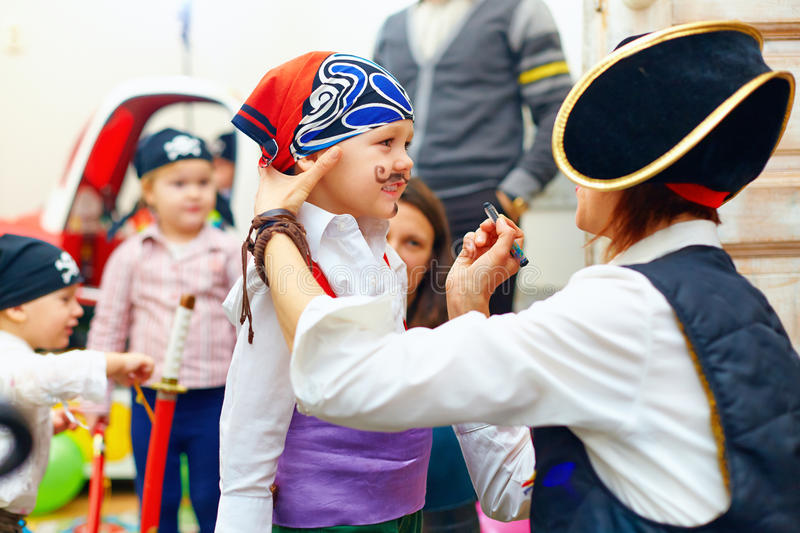 Woman painting kid's face on party royalty free stock photography