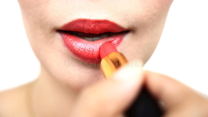 Woman painting a red lipstick, closeup, isolated, abstract, texture, on the white background stock image