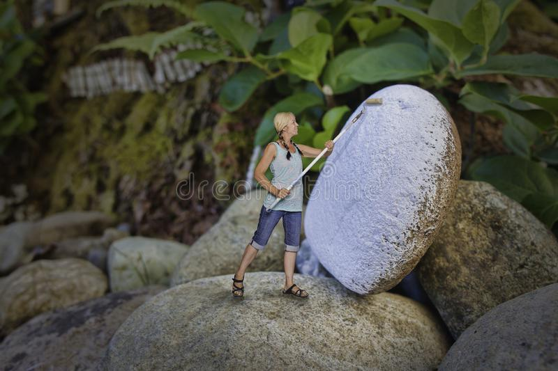 Woman painting rock stock photography