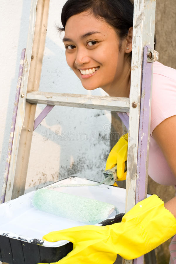 Woman painting with roller, gloves and ladder royalty free stock image