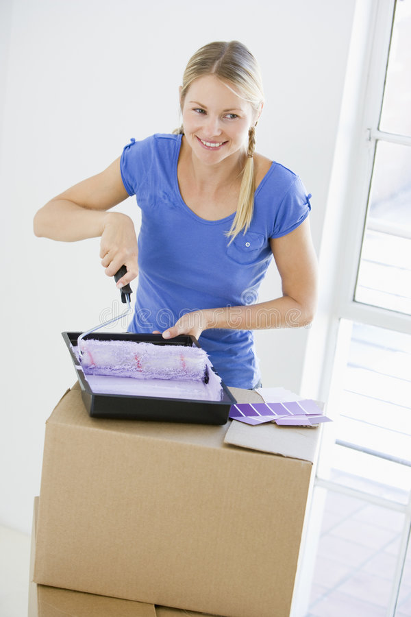 Woman painting room in new home smiling stock photo