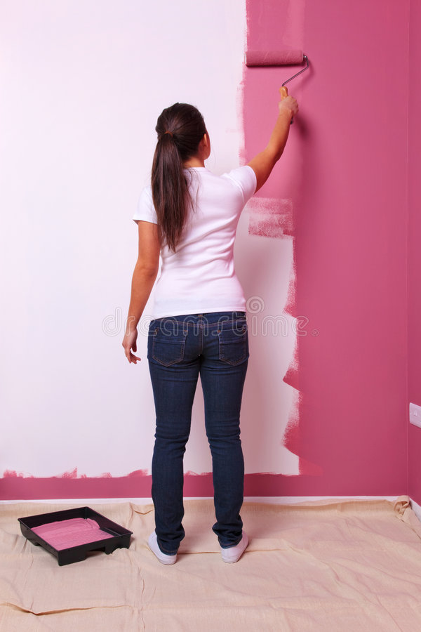 Woman painting a wall rear view royalty free stock images