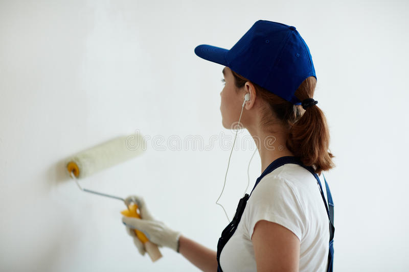 Woman Painting Walls with Music. Rear view portrait of young woman on construction site: female worker painting walls white using paint roller while remodeling stock photography