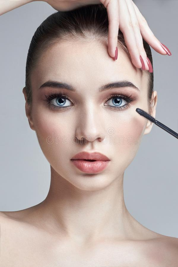 Woman paints eyelashes brush for the eyelashes. The increase in. Volume of eyelashes, cosmetics for eye care. Beautiful female face. Professional makeup with stock photos