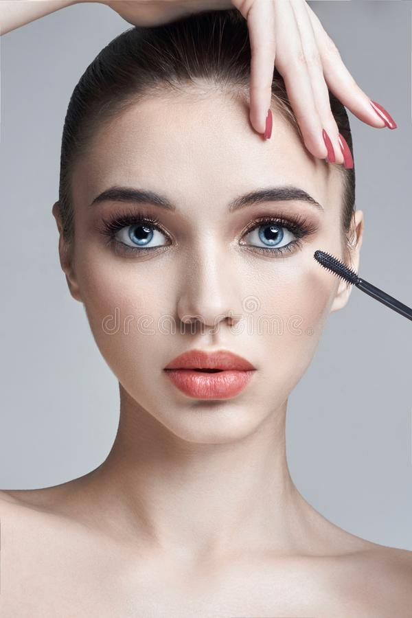 Woman paints eyes and eyelashes brush for eyelashes. Increase in volume of eyelashes, cosmetics for eye care. Beautiful female stock image