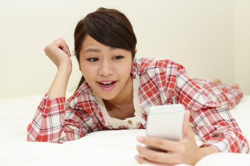 Woman in pajamas. Woman looking at smart phone stock photo
