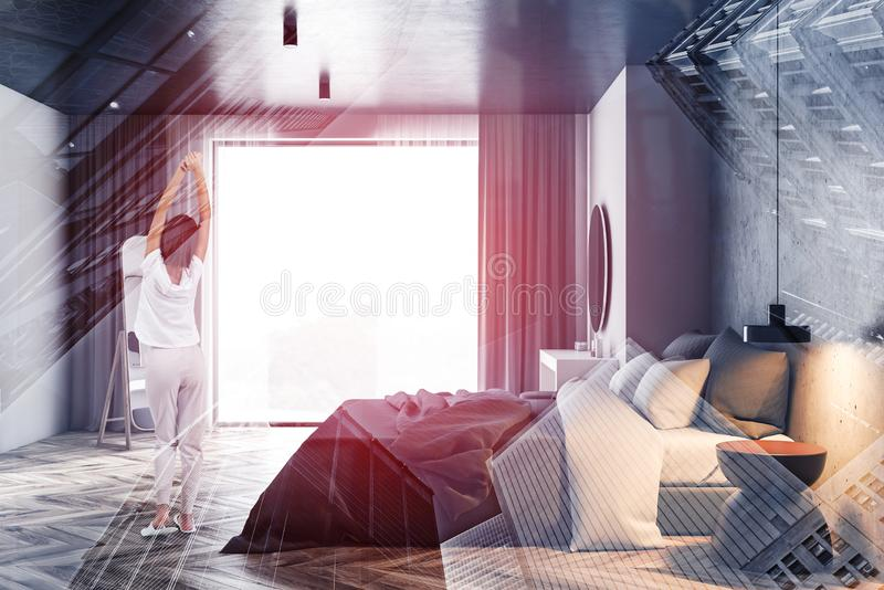 Woman in panoramic bedroom with mirror. Rear view of woman in pajamas standing in panoramic bedroom interior with wooden floor, master bed and makeup table with stock photography