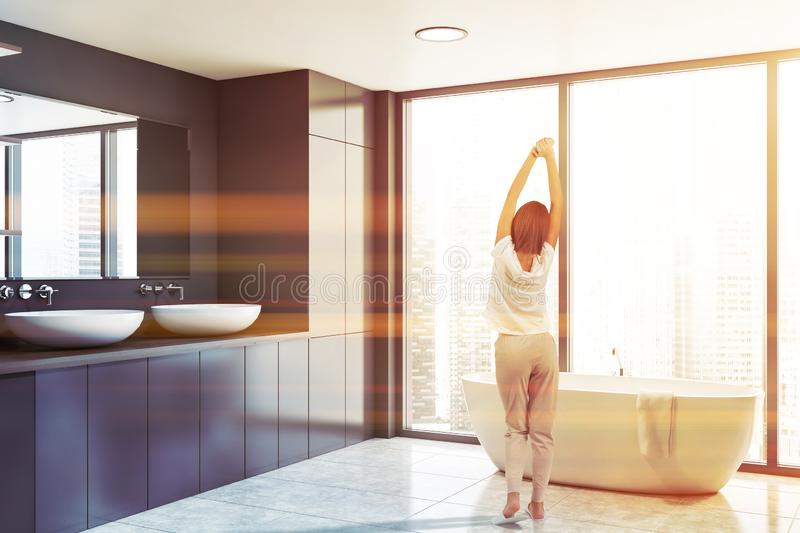 Woman in panoramic gray bathroom corner. Rear view of woman in pajamas standing in panoramic bathroom corner with gray walls, tiled floor, comfortable bathtub stock images