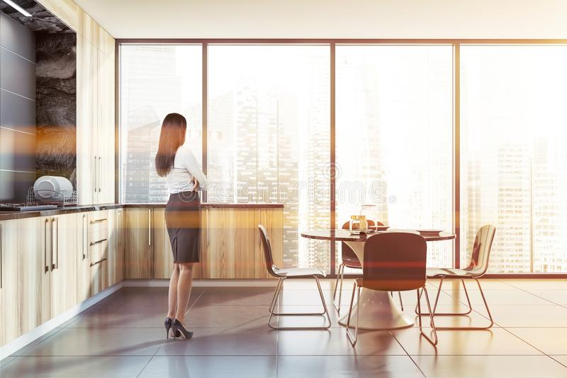 Woman in panoramic kitchen interior. Young woman with dark hair standing in modern kitchen with gray walls, panoramic window, wooden countertops with built in royalty free stock images