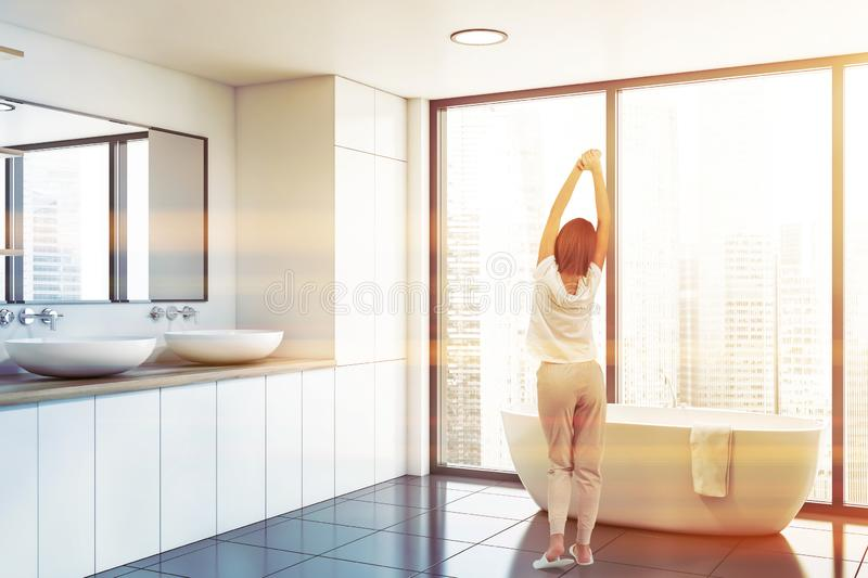 Woman in panoramic white bathroom corner. Rear view of woman in pajamas standing in panoramic bathroom corner with white walls, tiled floor, comfortable bathtub stock photo