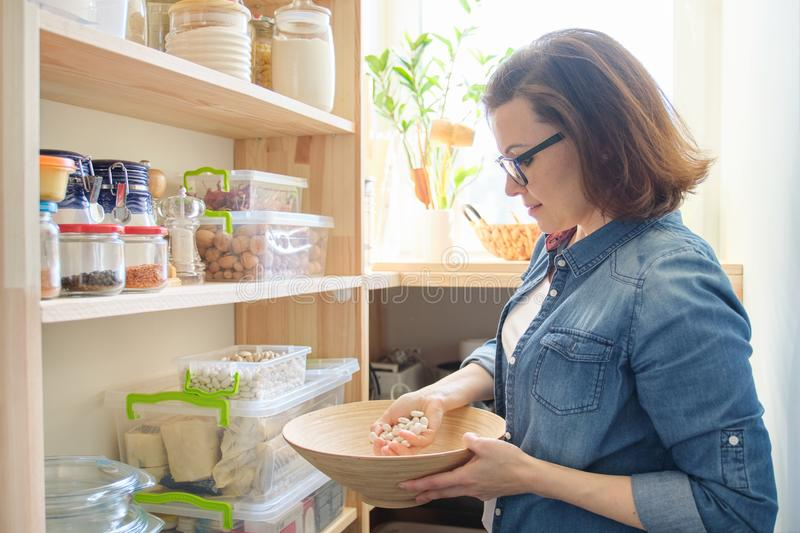 Woman in pantry with bowl of white beans. Storage cabinet in kitchen. With wooden shelves with food and utensils stock photos