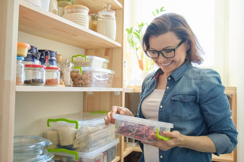 Woman in pantry holding container with red bitter chili pepper. Storage cabinet in kitchen. With wooden shelves with food and utensils stock image