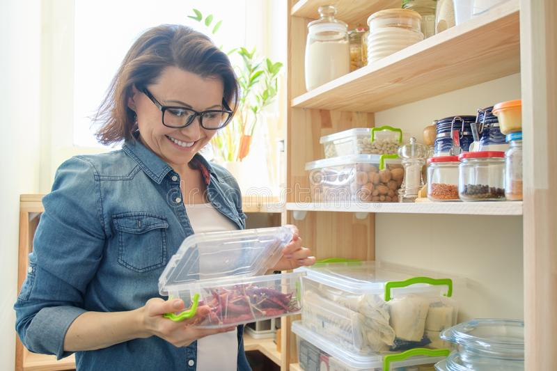 Woman in pantry holding container with red bitter chili pepper. Storage cabinet in kitchen. With wooden shelves with food and utensils royalty free stock photos