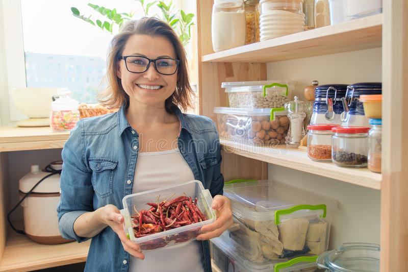 Woman in pantry holding container with red bitter chili pepper royalty free stock photography