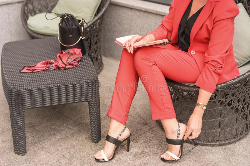 Woman in a pantsuit the color of live coral sits in a chair in sandals. Before the woman on the table royalty free stock photo