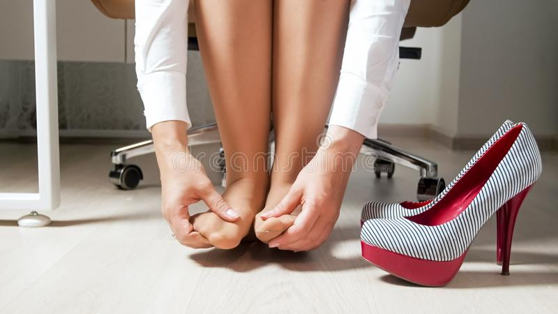 Young woman in pantyhose massaging and rubbing her feet and toes after wearing uncomfortable shoes royalty free stock image