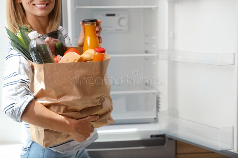 Woman with paper bag full of products near refrigerator in kitchen stock image