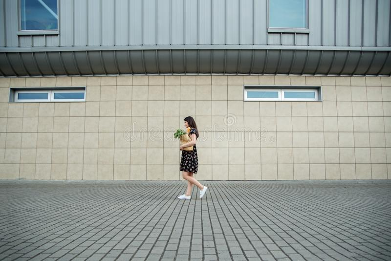 A woman with a paper bag near the supermarket. The concept of shopping, lifestyle. A woman with a paper bag near the supermarket. The concept of shopping, eco stock images