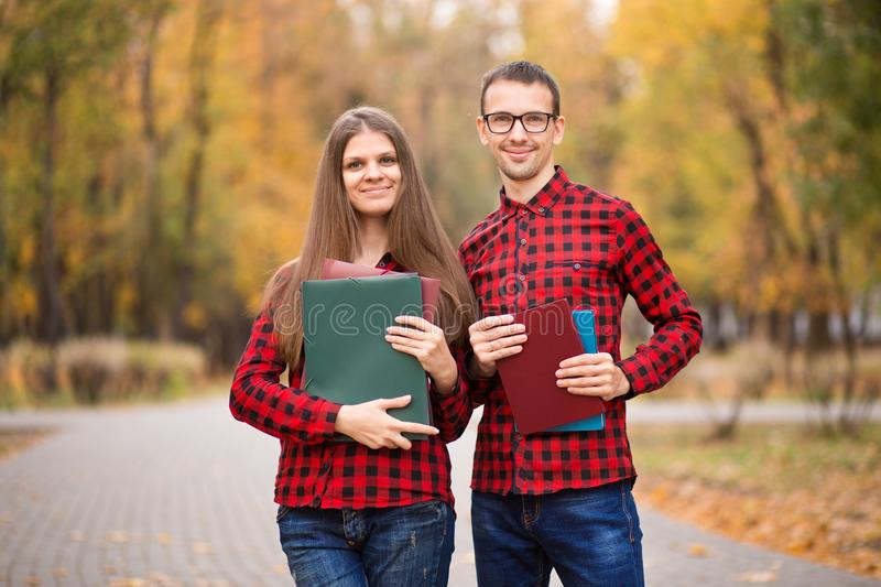 Woman with papers and engineers man discuss work in autumn park. stock photo