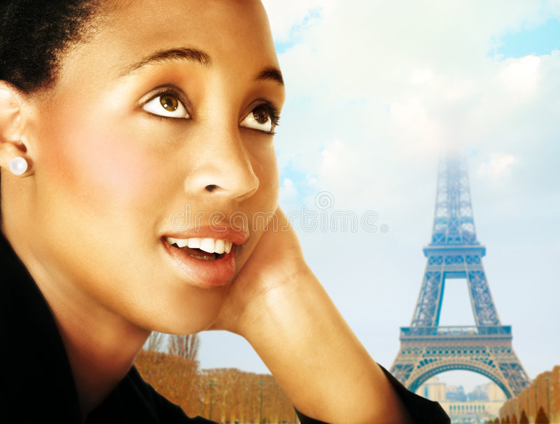 Woman and Paris. Young African woman in business suit dreaming about Paris - Eiffel tower in the background